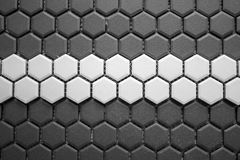 Ceramic tiles mosaic made of gray rhombuses with a white stripe in the middle, without grouting, the mesh-base and glue stock image