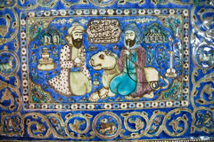 Ceramic tiles of 19th century with a lion & two persian men talking in garden Royalty Free Stock Images