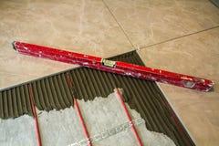 Ceramic tiles and tools for tiler. Floor tiles installation. Hom. E improvement, renovation - ceramic tile floor adhesive, mortar, level Royalty Free Stock Photo