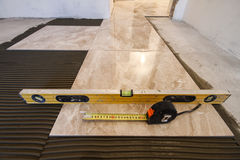 Ceramic tiles and tools for tiler. Floor tiles installation. Hom Royalty Free Stock Photography