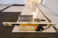 Ceramic tiles and tools for tiler. Floor tiles installation. Hom Royalty Free Stock Images