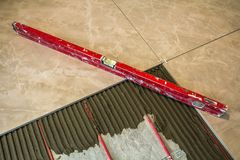 Ceramic tiles and tools for tiler. Floor tiles installation. Hom. E improvement, renovation - ceramic tile floor adhesive, mortar, level Stock Photo