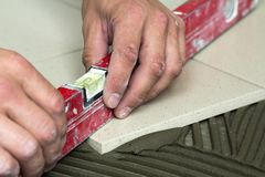 Ceramic tiles and tools for tiler. Worker hand installing floor Stock Photos