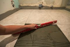 Ceramic tiles and tools for tiler. Worker hand installing floor tiles. Home improvement, renovation - ceramic tile floor adhesive,. Mortar, level Royalty Free Stock Photos