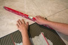 Ceramic tiles and tools for tiler. Worker hand installing floor tiles. Home improvement, renovation - ceramic tile floor adhesive,. Mortar, level Royalty Free Stock Image