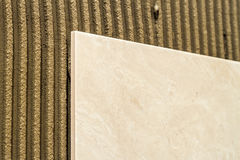 Ceramic tiles on a wall installation. Home improvement and renov Stock Image