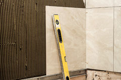 Ceramic tiles on a wall installation. Home improvement and renov Stock Photography