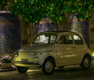 Ceramic tiles wall with old fiat car in Sorrento Amalfi Coast Italy. Night scene ceramic tiles mosaic wall with Fiat 500 retro old car parked under lemon street Stock Images