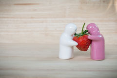 Ceramic toy giving a strawberry to couple for their love Royalty Free Stock Photography