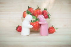 Ceramic toy giving a strawberry to couple for their love Royalty Free Stock Photos