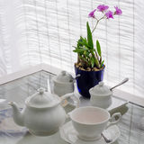 Ceramic utensils on table with flower decoration Stock Photography
