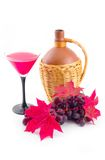 Ceramic vessel with red easy wine. And cluster of ripe sweet grapes on white background Royalty Free Stock Photo