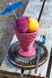 Ceramic vintage cup with fruit ice-cream sorbet balls served on. Ceramic vintage cup with fruit ice-cream sorbet balls served with paper umbrella on wooden plank royalty free stock photography
