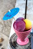 Ceramic vintage cup with fruit ice-cream sorbet balls served on. Ceramic vintage cup with fruit ice-cream sorbet balls served with paper umbrella on wooden plank royalty free stock images