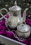 Ceramic vintage tea pot and cup with pink flower and necklace Royalty Free Stock Photos