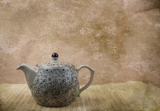 A ceramic vintage teapot on bamboo mat. Ceramic vintage teapot on a bamboo mat Royalty Free Stock Images