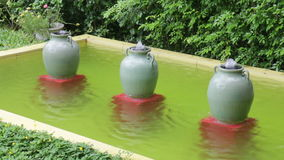 Ceramic water-filled jars decorated in outdoors garden stock video footage
