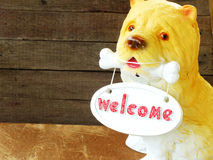 Ceramic welcome dog on wooden background Royalty Free Stock Image