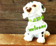 Ceramic welcome dog on wooden background Stock Image