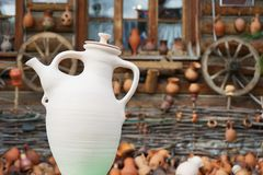 Ceramic white jug on the background of an old wooden house royalty free stock photos