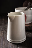 Ceramic white jug with red handle Stock Photos