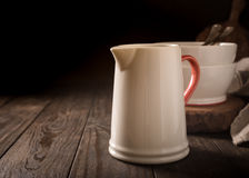 Ceramic white jug with red handle Stock Image
