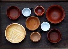 Ceramic, wooden, clay empty handmade bowl and cup on dark background. Pottery earthenware utensil, kitchenware. Royalty Free Stock Photography