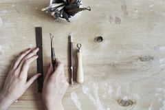 Ceramic working process, clay and tools for hand-crafted work. View from above, wooden table Stock Images
