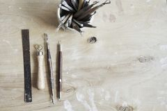 Ceramic working process, clay and tools for hand-crafted work. View from above, wooden table. Stock Photography