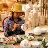 Ceramic workshop. HANOI, VIETNAM - SEP 24, 2014: Unidentified Vietnamese woman draws on the ceramic dish in the ceramic workshop. Ceramic art is very popular in Royalty Free Stock Images