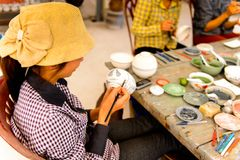Ceramic workshop. HANOI, VIETNAM - SEP 24, 2014: Unidentified Vietnamese woman draws on the ceramic dish in the ceramic workshop. Ceramic art is very popular in Royalty Free Stock Photography