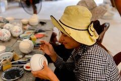 Ceramic workshop. HANOI, VIETNAM - SEP 24, 2014: Unidentified Vietnamese woman draws on the ceramic dish in the ceramic workshop. Ceramic art is very popular in Stock Image