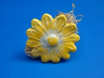 Ceramic yellow flower. On the blue background Royalty Free Stock Images