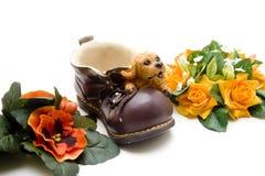 Ceramics dog on shoe with flowers Stock Photo