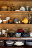 Ceramics and kitchen equipment on rustic wooden shelves Stock Image