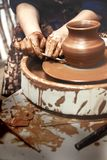 Ceramics. The master on the potter`s wheel produces a vessel of clay, undercutting the form. stock photo