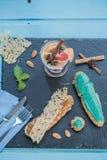 Ceramiczna kuchenka z eclairs z filiżanką świeża czarna kawa, dekorującą z migdałami, anyżem, cynamonem i mennicą na błękicie, Obraz Royalty Free