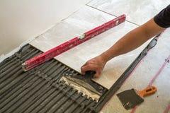 Ceramiczne płytki i narzędzia dla kaflarza Pracownik ręka instaluje podłogowe płytki Domowy ulepszenie, odświeżanie - ceramiczna  Zdjęcia Stock