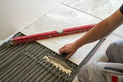 Ceramiczne płytki i narzędzia dla kaflarza Pracownik ręka instaluje podłogowe płytki Domowy ulepszenie, odświeżanie - ceramiczna  Obrazy Royalty Free