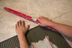 Ceramiczne płytki i narzędzia dla kaflarza Pracownik ręka instaluje podłogowe płytki Domowy ulepszenie, odświeżanie - ceramiczna  Zdjęcie Stock