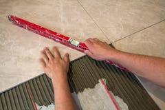 Ceramiczne płytki i narzędzia dla kaflarza Pracownik ręka instaluje podłogowe płytki Domowy ulepszenie, odświeżanie - ceramiczna  Obraz Royalty Free