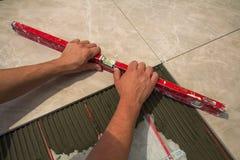 Ceramiczne płytki i narzędzia dla kaflarza Pracownik ręka instaluje podłogowe płytki Domowy ulepszenie, odświeżanie - ceramiczna  Obraz Stock