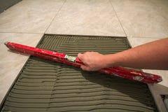 Ceramiczne płytki i narzędzia dla kaflarza Pracownik ręka instaluje podłogowe płytki Domowy ulepszenie, odświeżanie - ceramiczna  Zdjęcia Royalty Free