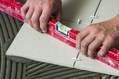 Ceramiczne płytki i narzędzia dla kaflarza Pracownik ręka instaluje podłogowe płytki Domowy ulepszenie, odświeżanie - ceramiczna  Zdjęcie Royalty Free