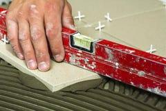 Ceramiczne płytki i narzędzia dla kaflarza Pracownik ręka instaluje podłogowe płytki Domowy ulepszenie, odświeżanie - ceramiczna  Obrazy Stock