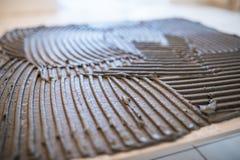 ceramiczne target1908_0_ płytki Troweling adhezyjny dla ceramicznej płytki podłoga obraz stock