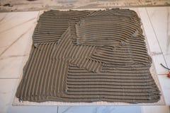 ceramiczne target1908_0_ płytki Troweling adhezyjny dla ceramicznej płytki podłoga zdjęcie royalty free