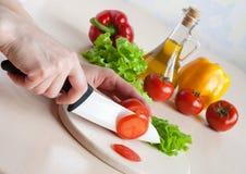 ceramicznej rozcięcia ręki nożowi sałatkowi pomidory fotografia royalty free