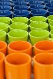 Ceramiczni kubki i puchary różni kolory w sklepie na kontuarze, stoją z rzędu palowego Sprzedaż, handel Obrazy Royalty Free
