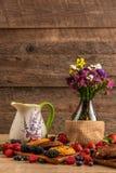 Ceramiczny garnek, szklana waza z kwiatami i ciastka, dobieraliśmy z mieszanką dzikie jagody fotografia royalty free